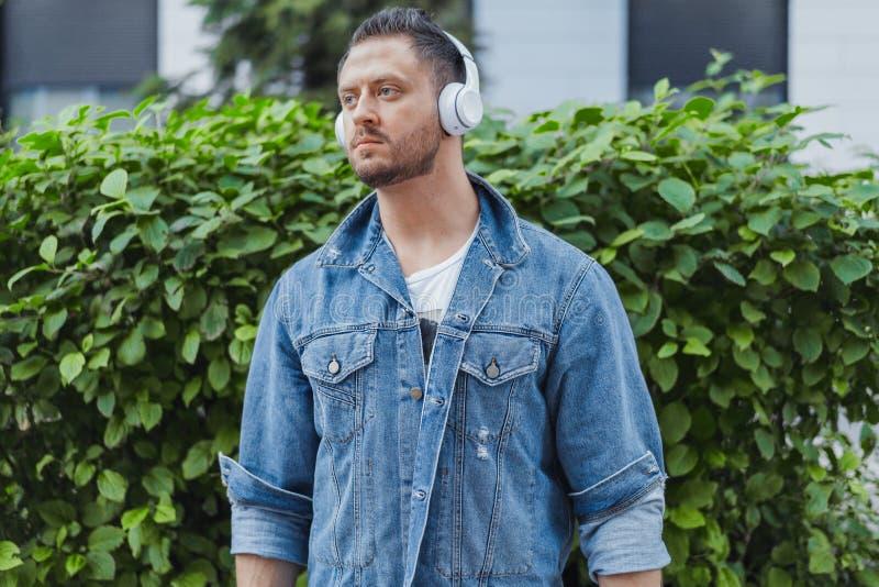 关闭听到在耳机的音乐的年轻可爱的人在都市风景 免版税库存照片