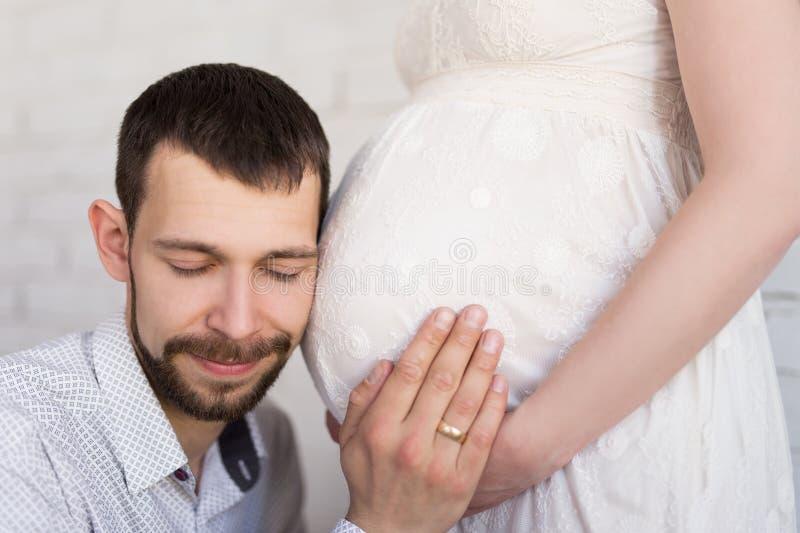 关闭听年轻英俊的人他的pregna的腹部 免版税图库摄影