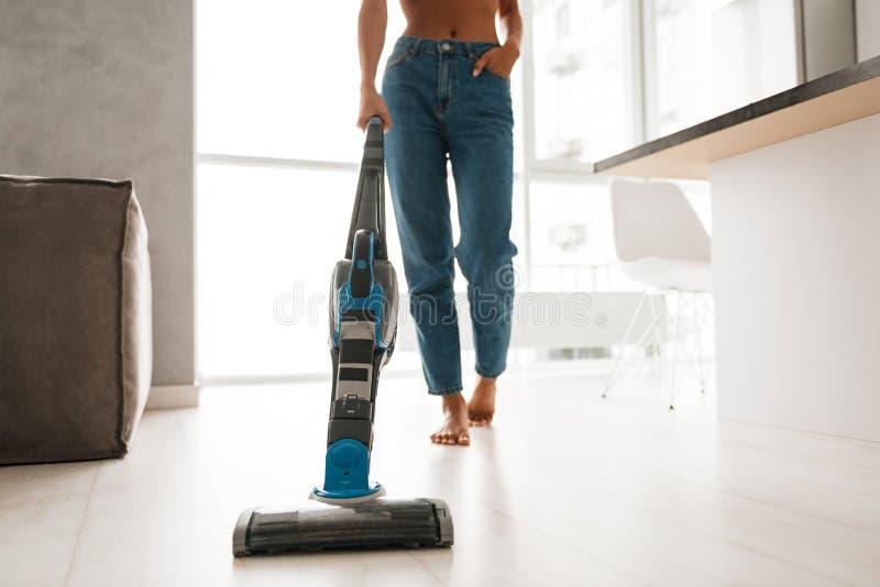 关闭吸尘地板的牛仔裤的一个少妇 免版税库存照片