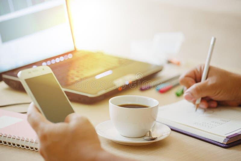 关闭咖啡和便携式计算机用商人的手使用巧妙的电话的 库存照片