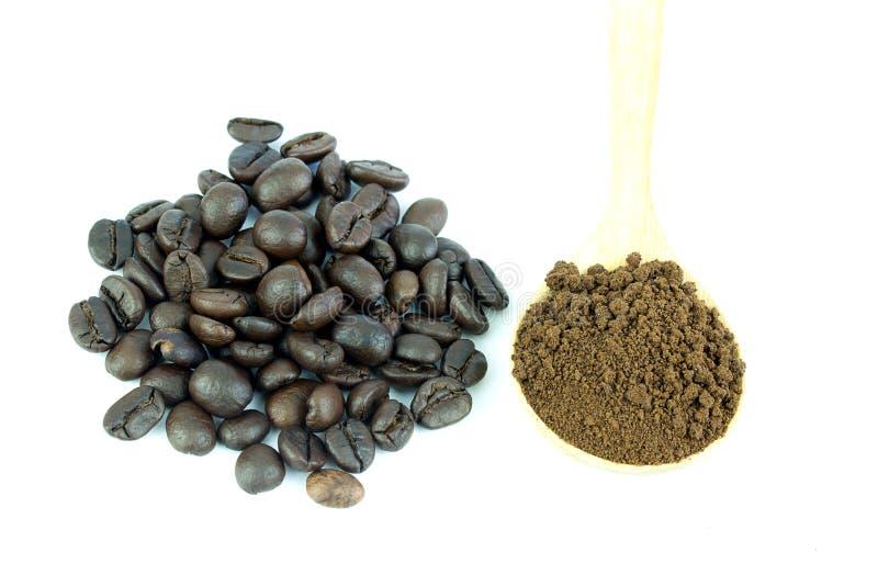 关闭咖啡豆和咖啡粉末在木匙子 库存图片