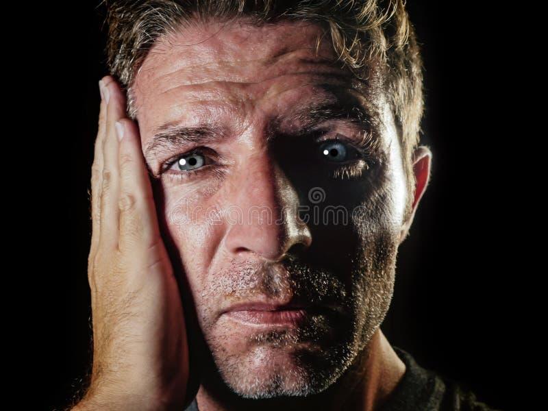关闭哀伤和沮丧的人画象用在看起来绝望感觉的面孔的手被挫败和无能为力在消沉和s 图库摄影