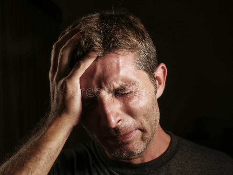 关闭哀伤和沮丧的人画象用在看起来绝望感觉被挫败和无能为力哭泣的面孔的手凄惨  库存图片