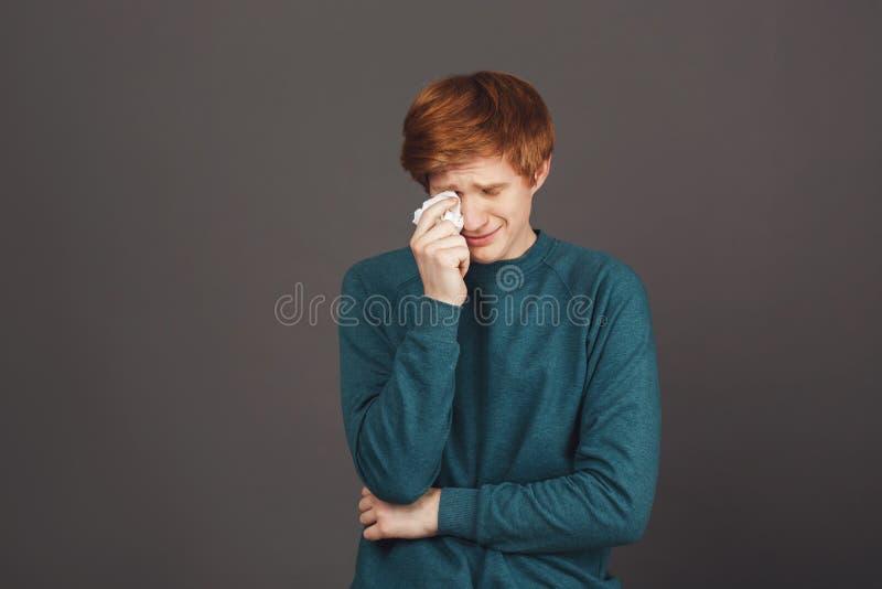 关闭哭泣绿色毛线衣的年轻英俊的敏感姜的少年,与纸巾的抹泪花,疲乏 免版税库存照片