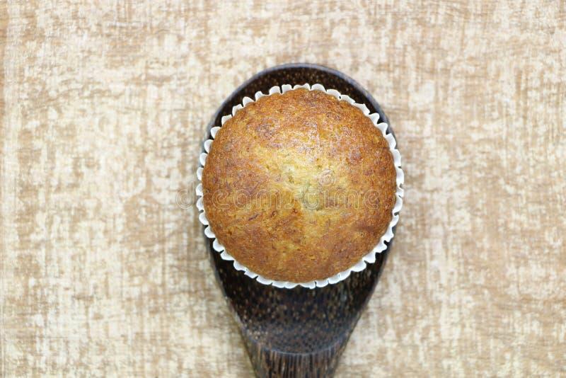 关闭唯一在木杓子看起来的香蕉杯子蛋糕面包店顶视图可口在木桌背景 免版税库存图片