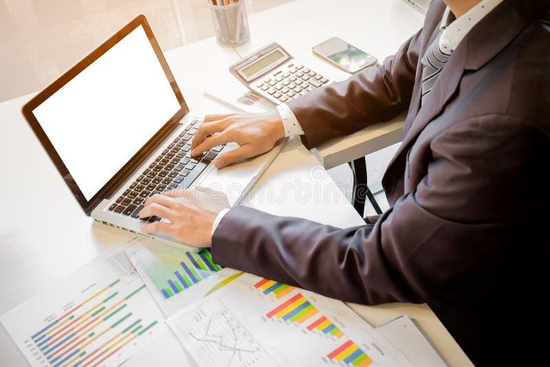 关闭商人工作文件和膝上型计算机的手  免版税库存图片