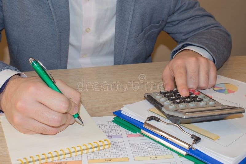 关闭商人手运作在计算器,会计文件在办公室,电子商务概念的候宰栏 库存照片