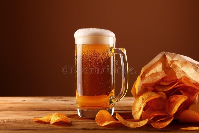 关闭啤酒杯和土豆片在褐色 免版税库存照片