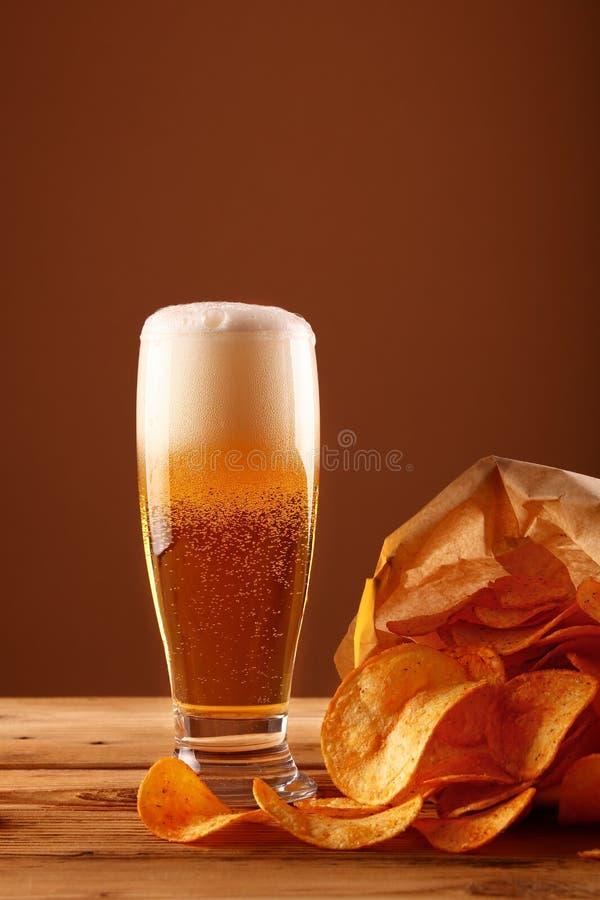 关闭啤酒杯和薯片在褐色 图库摄影