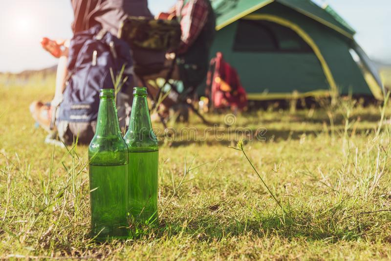 关闭啤酒瓶在草甸,当野营在户外时 Hol 免版税库存照片