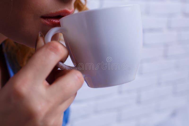 关闭喝从美好的w的少妇肉欲的嘴唇咖啡 图库摄影