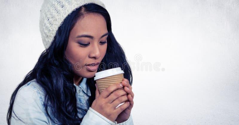 关闭喝从咖啡杯的妇女对白色墙壁 库存图片