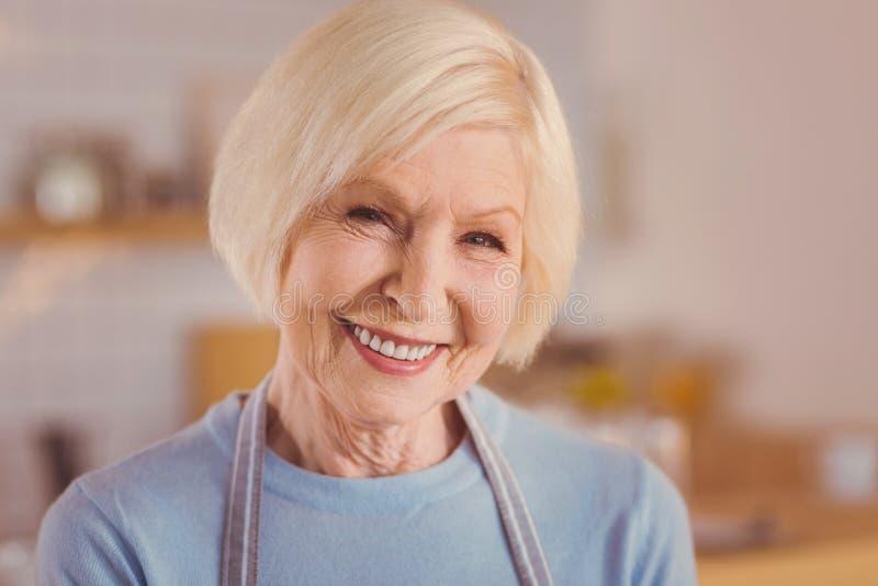 关闭围裙的美丽的年长妇女 库存照片