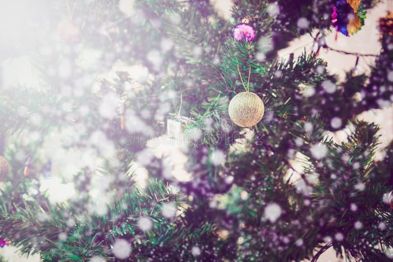 关闭圣诞快乐和新年快乐在关闭装饰的树有雪bokeh背景 免版税图库摄影