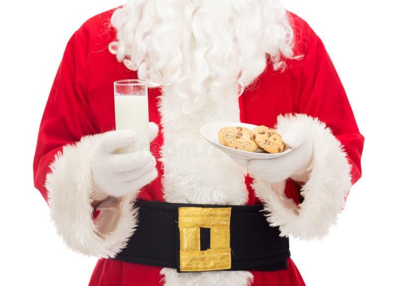 关闭圣诞老人用牛奶和曲奇饼 免版税图库摄影