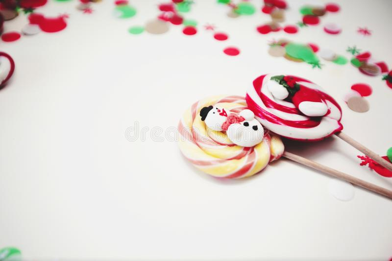 关闭圣诞节镶边的和色的棒棒糖 在白色背景的糖果与五彩纸屑 免版税库存图片