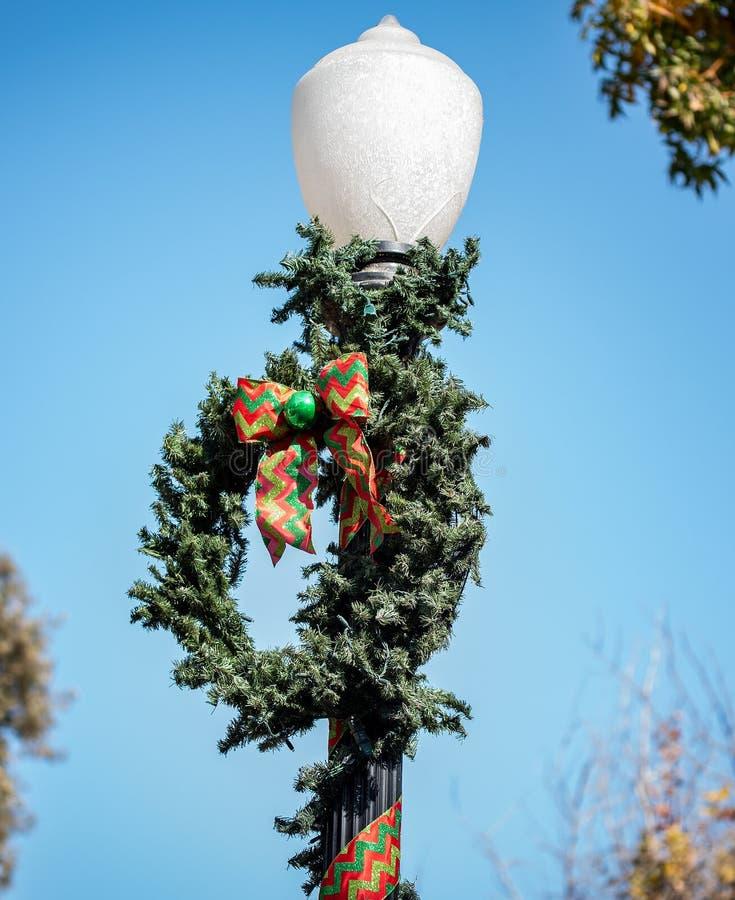 关闭在一个轻的岗位的圣诞节花圈 免版税图库摄影
