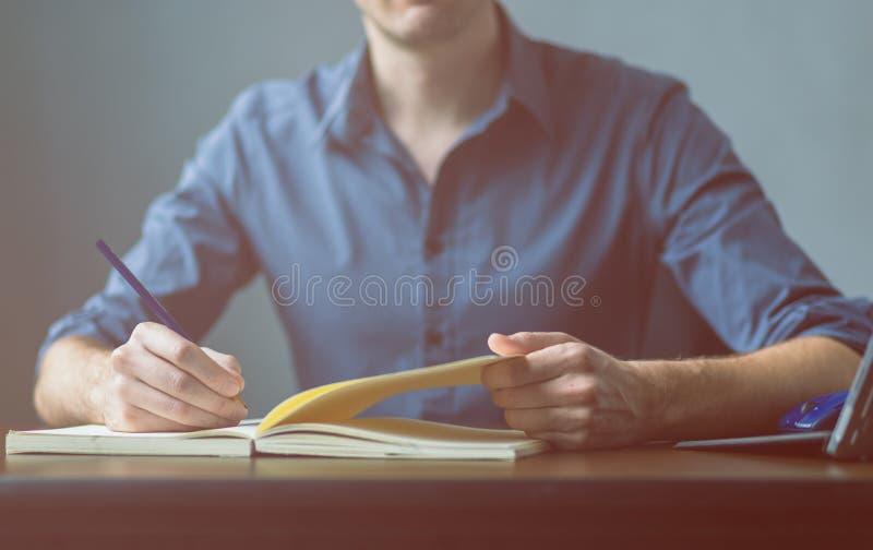 关闭在一件蓝色衬衣的签署或写文件的一个商人的手在笔记本板料  库存图片
