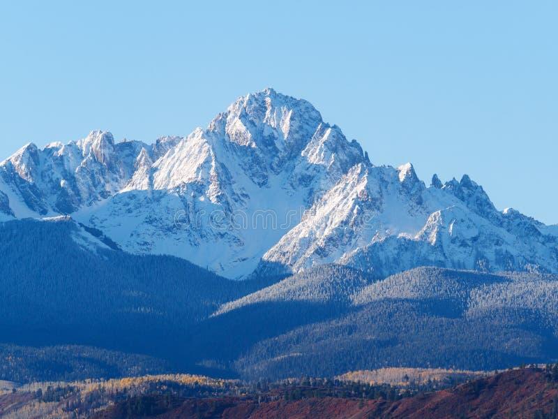 关闭在一明亮白天蓝色的积雪的Sneffels范围 库存照片