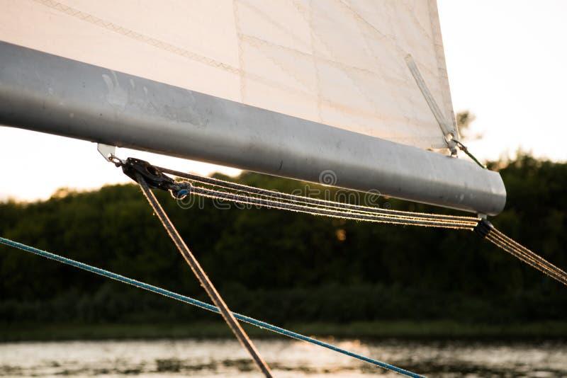 关闭在一条航行的游艇的景气帆柱,有风帆和索具绳索的和河或湖海岸在背景中 免版税库存图片