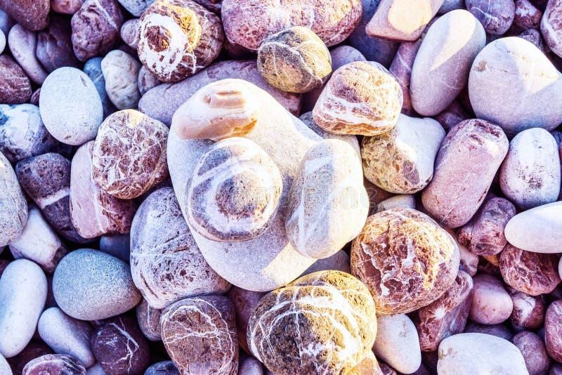 关闭在不同的大小的桃红色和灰色镶边石头与落在他们的太阳的射线的 库存图片