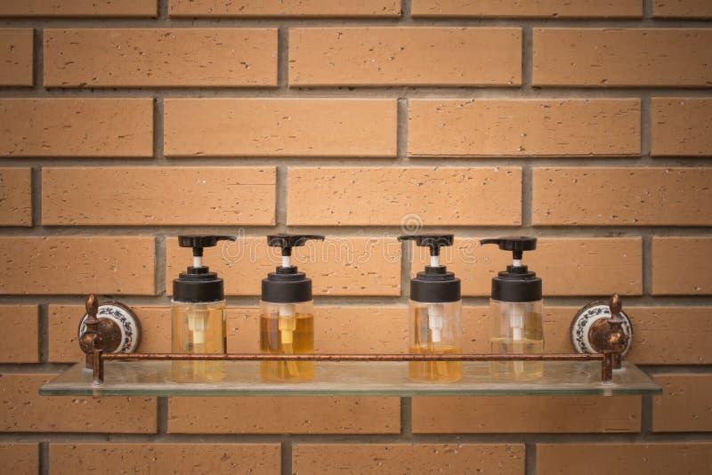 关闭在与砖墙的玻璃架子上把放的适应的香波和阵雨奶油瓶在游泳场旁边的背景 库存图片
