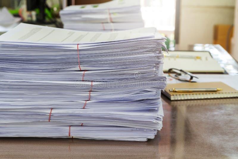 关闭在书桌,报告纸叠上的商业文件堆 库存照片