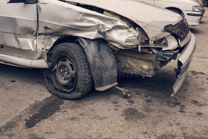 关闭在交通事故以后的一辆残破的汽车在停车场离开 一台防撞器和一个轮子的重的损伤在a以后边在col 库存照片