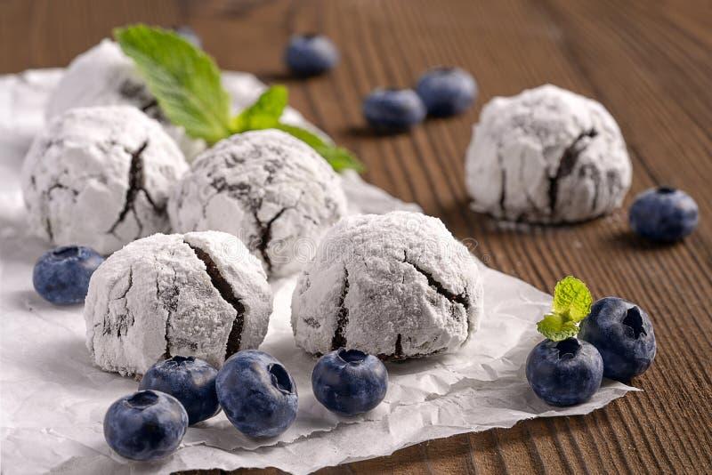关闭在供给动力的糖结冰的皱纹巧克力饼干用在一张烘烤的纸的蓝莓 免版税库存照片