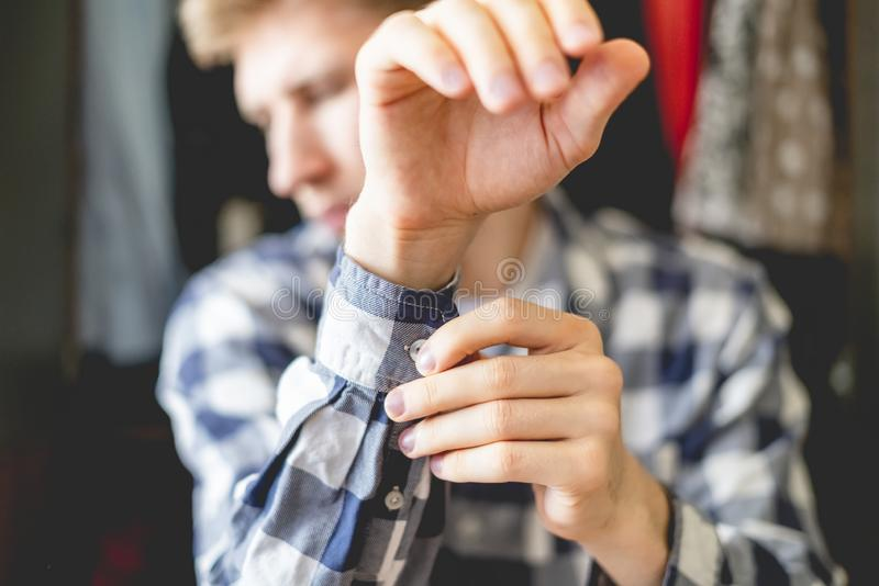 关闭在偶然衬衣上在家把放的年轻人,调整的按钮f的袖子关闭 免版税库存照片