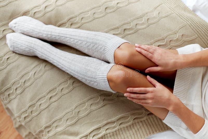 关闭在冬天膝盖袜子的妇女腿在床上 库存图片