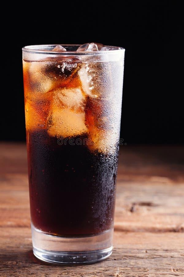 关闭在刷新与冰的寒冷软饮料在黑暗的木背景 免版税库存照片