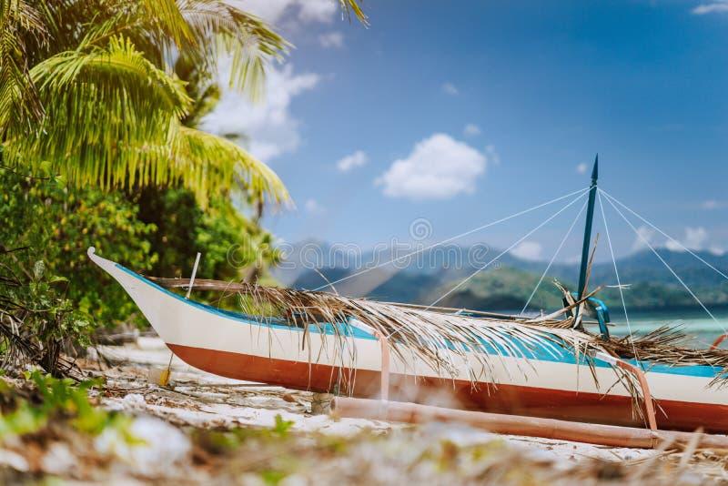 关闭在前面的木地方banca小船在用干燥棕榈叶盖的热带海滩,美丽如画的风景在 库存图片