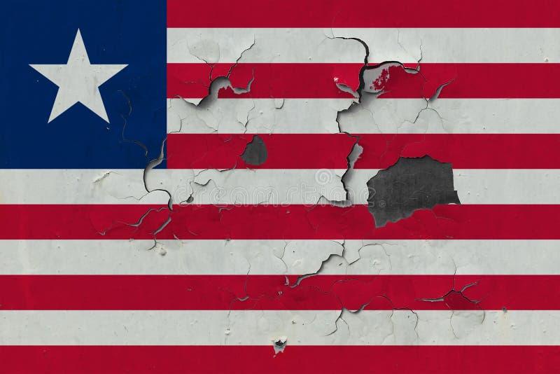 关闭在剥皮油漆的墙壁上的脏,损坏的和被风化的利比里亚旗子看叉瓦的基面 免版税库存图片
