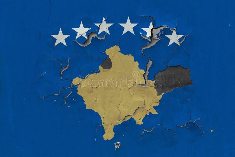 关闭在剥皮油漆的墙壁上的脏,损坏的和被风化的科索沃旗子看叉瓦的基面 免版税库存照片