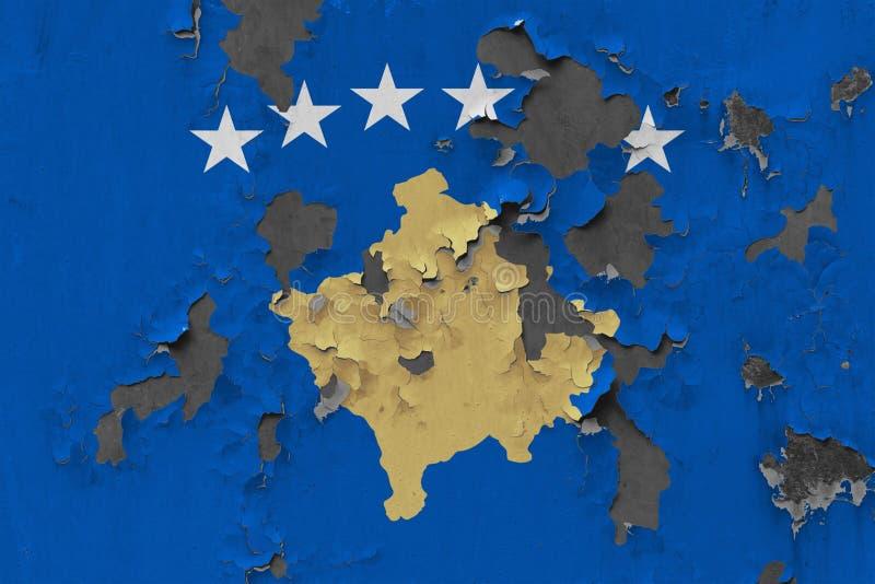 关闭在剥皮油漆的墙壁上的脏,损坏的和被风化的科索沃旗子看叉瓦的基面 免版税库存图片