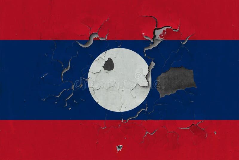 关闭在剥皮油漆的墙壁上的脏,损坏的和被风化的老挝旗子看叉瓦的基面 免版税库存照片