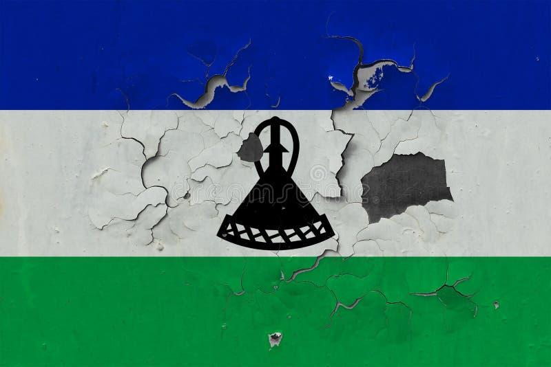 关闭在剥皮油漆的墙壁上的脏,损坏的和被风化的莱索托旗子看叉瓦的基面 免版税库存照片
