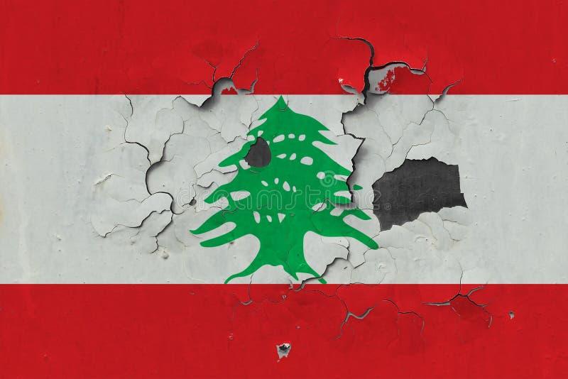 关闭在剥皮油漆的墙壁上的脏,损坏的和被风化的黎巴嫩旗子看叉瓦的基面 免版税库存图片