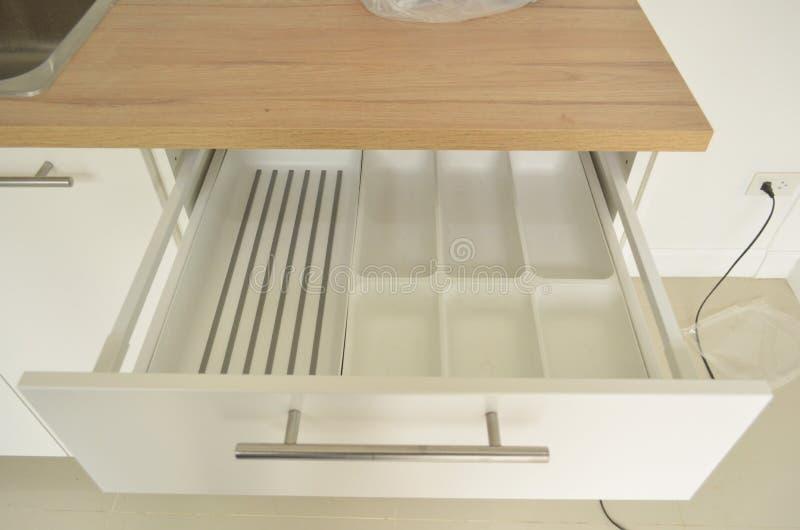 关闭在厨房家具的白色匙子盘子 免版税库存照片