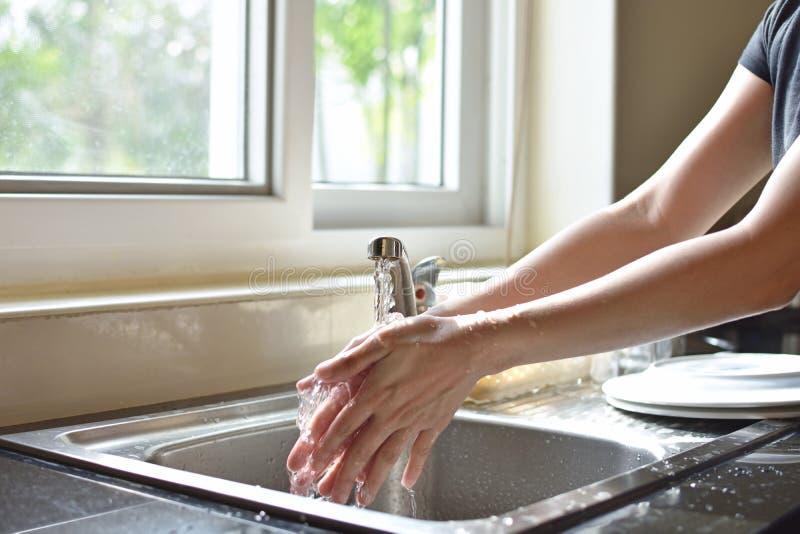 关闭在厨房水槽的妇女洗涤的手 免版税库存照片