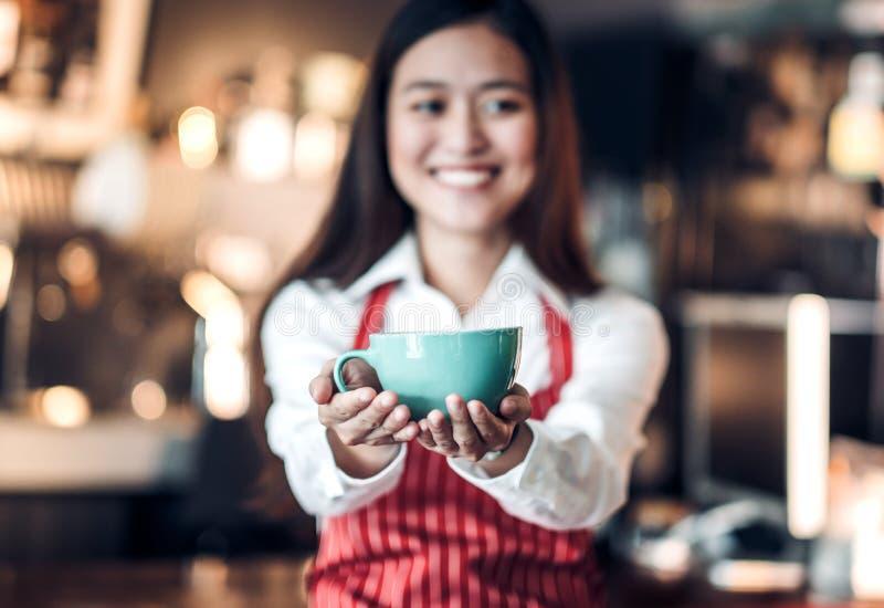 关闭在咖啡与拿着杯子的迷离亚洲妇女barista 库存照片