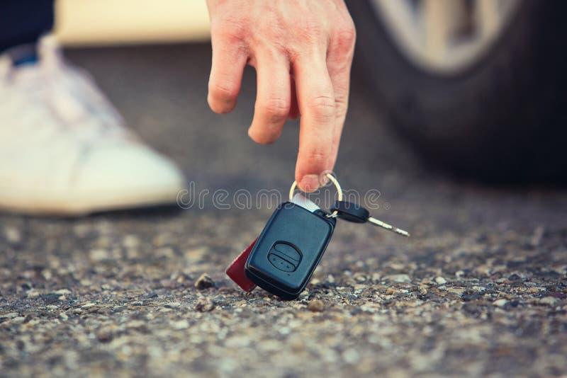 关闭在地面上下落的人手举的汽车钥匙 人发现车钥匙某人在停车处的柏油路丢失了 免版税图库摄影