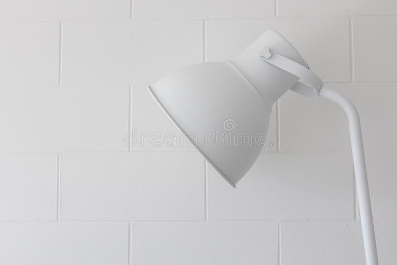 关闭在块砖墙纹理背景的可调整的唯一简单的现代白色灯 免版税库存图片