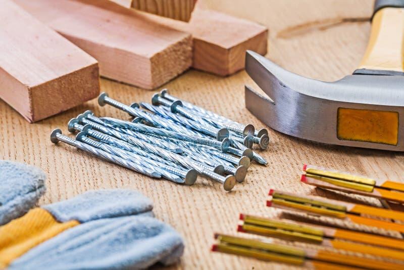关闭在套的看法木匠业工具锤子钉子手套米 免版税库存照片