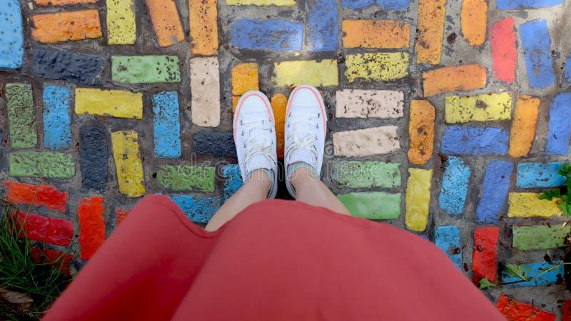 关闭在女孩佩带白色运动鞋的` s脚站立在Coloful瓦片 免版税库存照片
