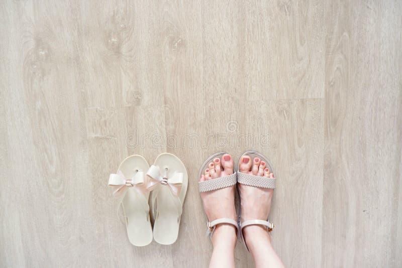 关闭在妇女是穿弓鞋子隔绝在木地板上,时兴的辅助部件的脚 时尚平的鞋子鞋类 Selfie 库存照片