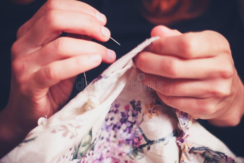 关闭在妇女的手缝合 免版税库存照片