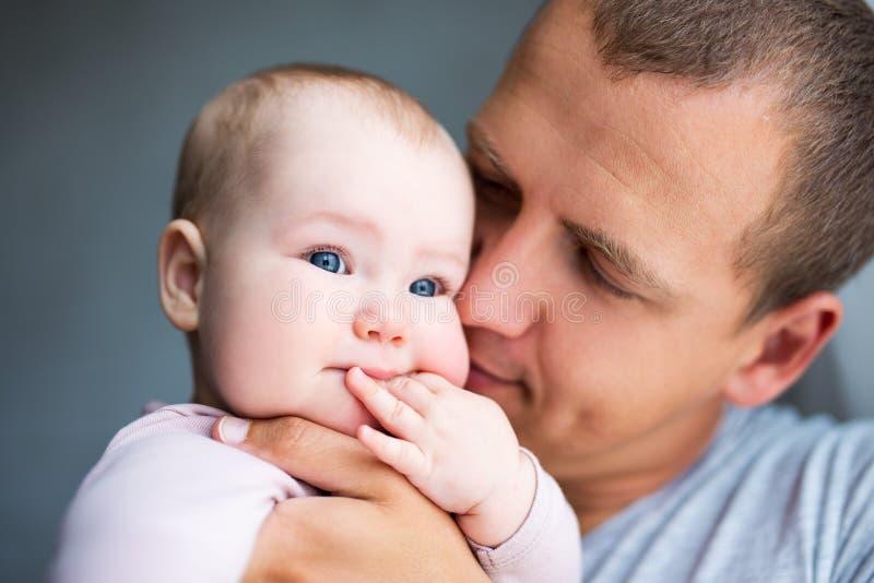 关闭在家亲吻女婴的年轻父亲画象 库存图片