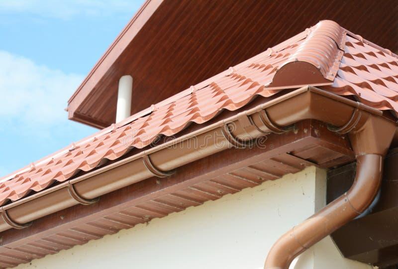 关闭在屋顶天沟持有人和guttering的水落管管子有黏土瓦屋顶的 安装雨的天沟 图库摄影